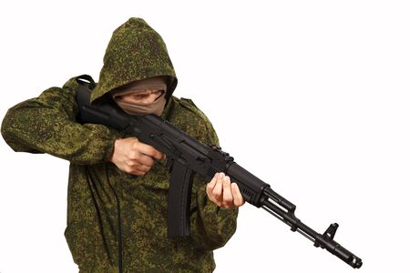 The man in a mask and a hood on the head keeps in a military green jacket about the automatic machine AK-74 Kalashnikov weapon on a white background, a close up Stock Photo