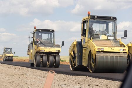 TAGANROG, RUSSIA - June 26, 2017: The asphalt paver asphalts the road, on the street stacks new asphalt against the background of the blue sky in the summer day Éditoriale