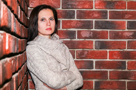 Humeral portrait. The serious young woman the brunette in a brown knitted sweater has leaned the elbows on a brick red wall indoors  版權商用圖片