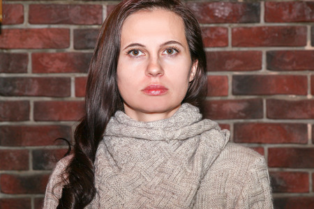 The young woman the brunette with serious, a look in a brown knitted sweater against the background of a brick red wall