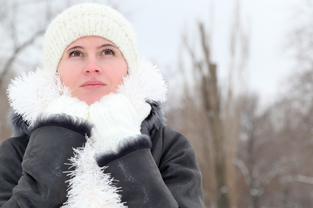 The young woman keeps hands at a neck in a white knitted cap, mittens and a sheepskin coat with New Years tinsel on the street in the winter Stock Photo