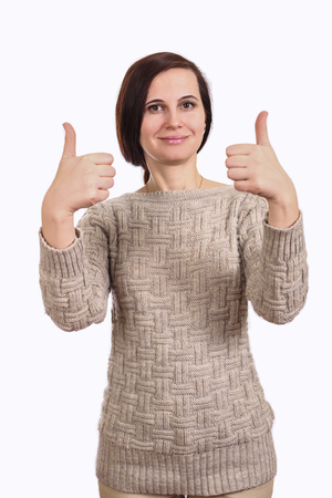 Portrait of the girl of the brunette in a sweater. The gesture a thumb is lifted up