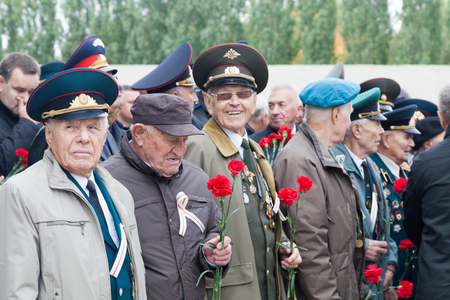 VOLGOGRAD, RUSSIA - October 15, 2017: Group of old military pensioners in a military uniform, awards and medals stand holding flowers to a tack in hand