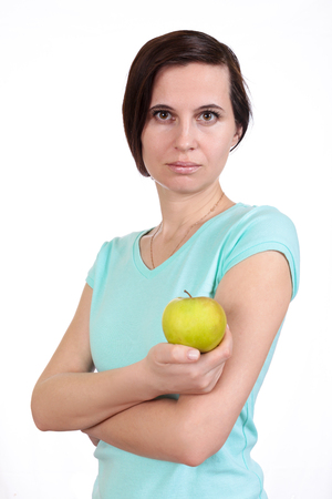 The girl in a t-shirt holds fingers apple in hand. The isolated white background