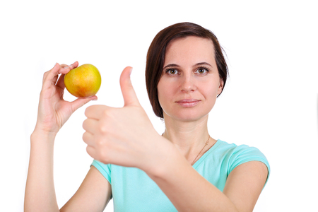 The girl to a t-shirt keeps in summer clothes hand fingers apple, other hand the thumb up, on the isolated white background shows gesture of OK