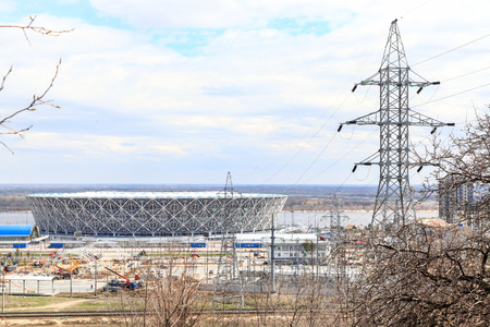 VOLGOGRAD, RUSSIA - April 21, 2018: A high-voltage support of the power line, behind him the Arena stadium Stockfoto - 105295089