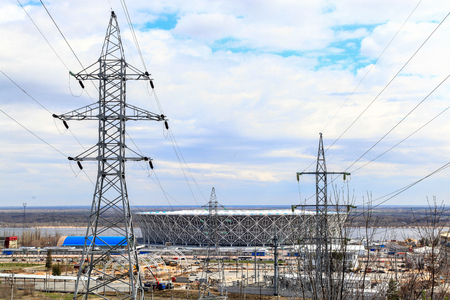 VOLGOGRAD, RUSSIA - April 21, 2018: A high-voltage support of the power line, behind him the Arena stadium
