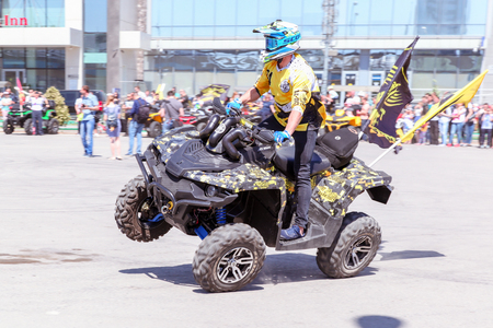 VOLGOGRAD, RUSSIA - May 5, 2018: The motorcyclist carries out tricks on the four-wheel motorcycle the ATV, on the square in front of Europe shopping Center