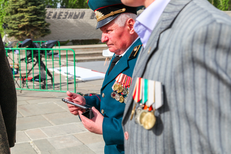 VOLGOGRAD, RUSSIA - May 9, 2018: The elderly man in the Russian military uniform goes with awards and medals down the street. A look with a side 에디토리얼