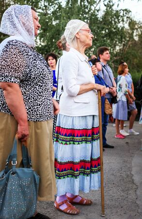 VOLGOGRAD, RUSSIA - July 25, 2018: Portrait of two elderly women looking forward on the street in the park among people to the utmost. A look with a side