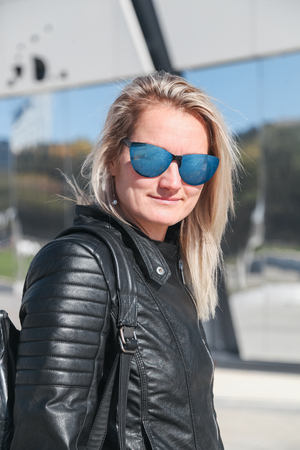 The woman in jeans, a leather jacket, sunglasses. A portrait on a belt