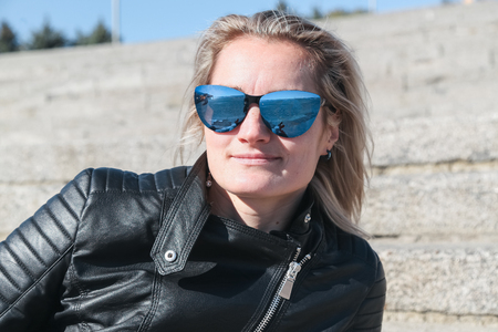 The womans portrait in a black leather jacket, sunglasses, outdoors. Clear sunny autumn day