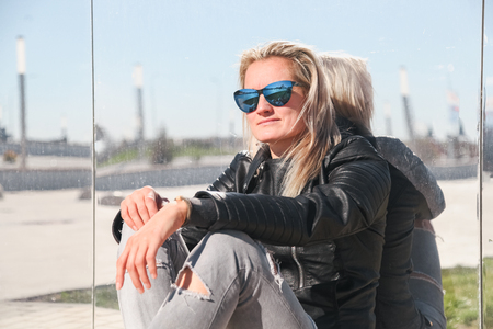 The woman sits having crossed legs on asphalt in jeans, a leather jacket, sunglasses on the city street