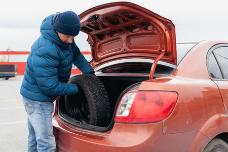 The man in a warm winter jacket puts a wheel in a car luggage carrier Standard-Bild