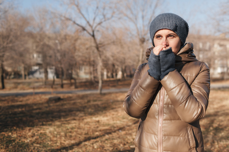 The woman froze in the park. Warms hands with breath from a mouth. A portrait on a belt 免版税图像
