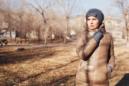 The woman in the autumn park. Holds the right hand about a neck. A portrait on a belt
