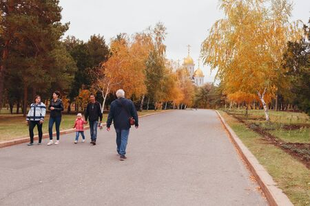 VOLGOGRAD, RUSSIA - 21 October, 2018: People walk on the asphalted road in the park overlooking Church of All Saints church on Mamayev Kurgan in the fall, Volgograd Editorial