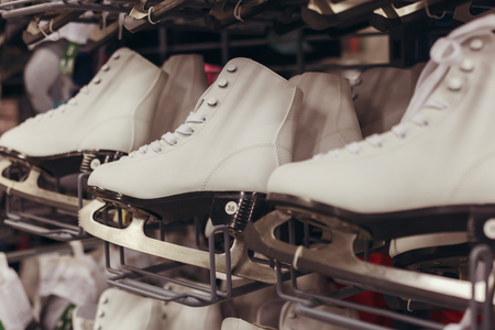 White skates stand for sale on the shelf of shop