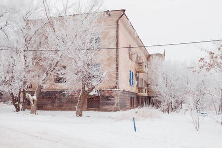 Old brick two-storeyed Stalin house in the winter, among snow. A