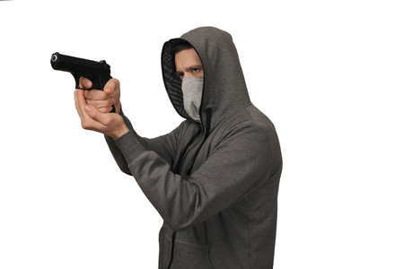 The man in a sports jacket and in a mask shoots with the gun Banco de Imagens