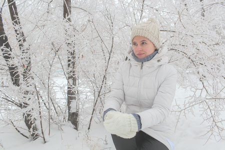 The girl is in the park in the winter among snow