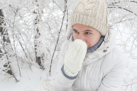The girl to stand in the park in the winter among snow. A mitten closes a nose Banco de Imagens