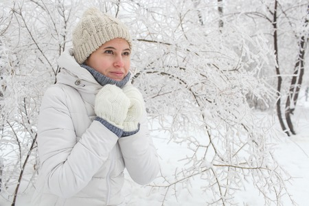 The girl to stand in the park in the winter among snow. Hands about a neck Banco de Imagens