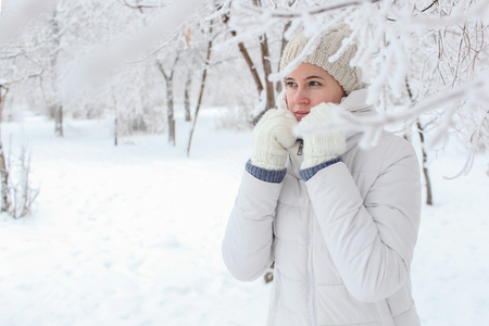 The girl to stand in the park in the winter among snow. Hands about the head Banco de Imagens