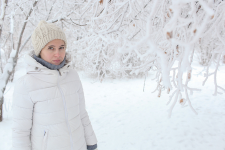 The girl to stand in the park in the winter among snow Banco de Imagens