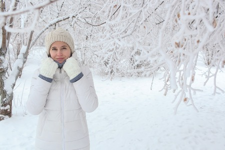 The girl walks in the park in the winter among snow. Hands at the head Banco de Imagens