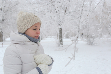The girl walks in the park in the winter. A portrait on a belt, a look with a side