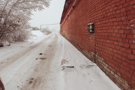 The winter dirt road in snow along a red brick wall