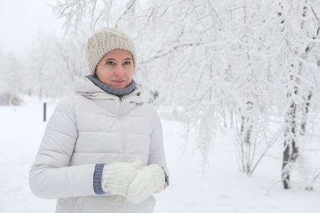 The girl walks in the park in the winter among snow. A portrait on a belt Banco de Imagens