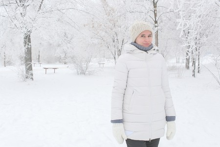 The girl walks in the park in the winter among snow. A portrait up to a hip