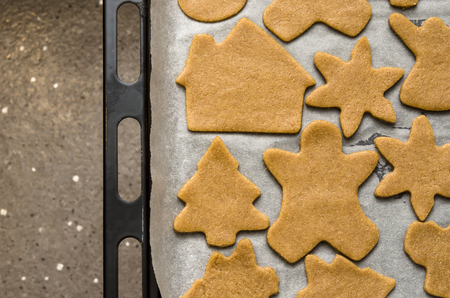 Home-baked gingerbread on a kitchen surface with a baking sheet and baking paper - Christmas concept with home-baked cookies in the kitchen.