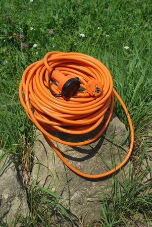 Orange electric cable in the grass photo