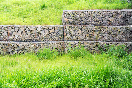 gabion mesh: Wire mesh reinforcement with rock and green grass
