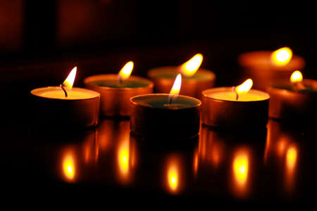 cultic: Rows of burning candles in a dim church.