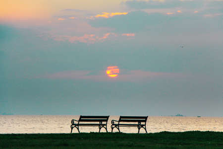 Empty benches at the beach front at sunset. photo