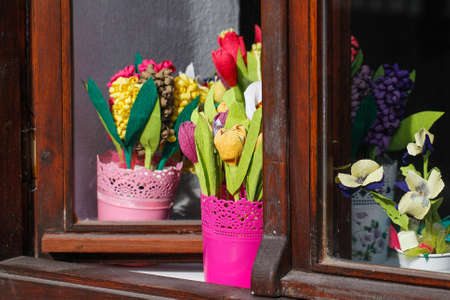 Flowers in pots. Flowers of handicraft papyrus. Colorful flowers in window. photo