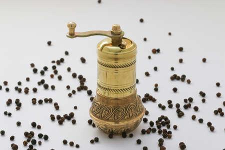 pepper grinder: Copper pepper mill. Brass pepper mill. Old copper pepper grinder with pepper grains isolated on white. Stock Photo