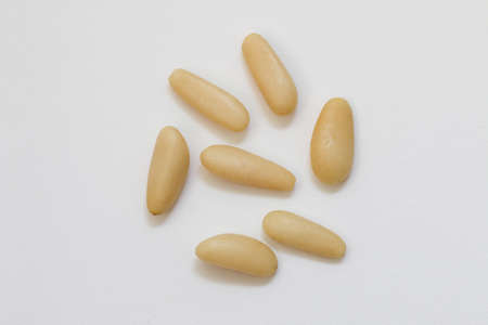 Pine nuts isolated on white. Pine nuts in close up.