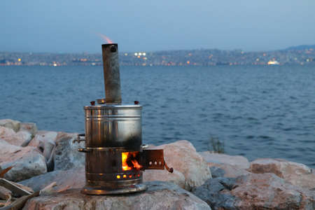 marina life: Ancient copper samovar on the shore. Boiling old samovar. Stock Photo