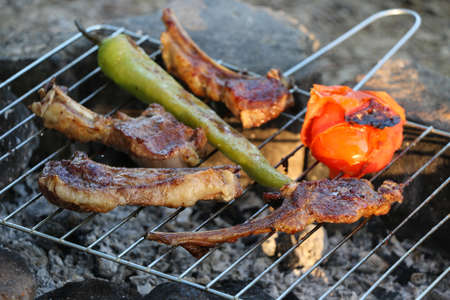 scored: Grilled pork steaks on the grill. Lamb chops on grill with tomatoes and peppers. Stock Photo