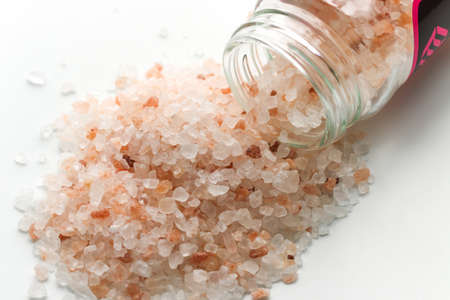 Himalayan pink salt in small jar of glass. Himalayan salt pile on white background. Pink crystal salt isolated on white background. Close up of Himalayan salt - pink and orange coarse crystals. Stock Photo