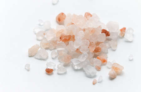 Pink Himalayan salt. Himalayan salt pile on white background. Pink crystal salt isolated on white background. Close up of Himalayan salt - pink and orange coarse crystals.