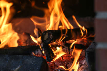 Close up shot of burning firewood in the fireplace in the house. Cosiness.