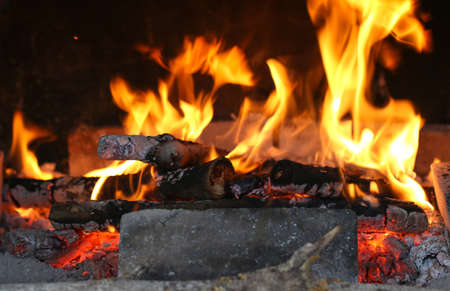 Close up shot of burning firewood in the fireplace in the house. Cosiness. Stock Photo