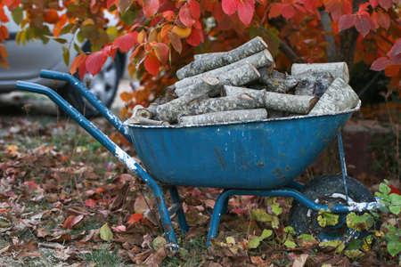 Brennholz liegt in einer Schubkarre, bereit für ein Feuer. Bunte Herbstgarten. Vorbereitung für den Winter.