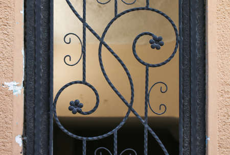 iron curtain: Part of forged gate. Beautiful metal work with floral elements. Black metal on pastel background. Stock Photo